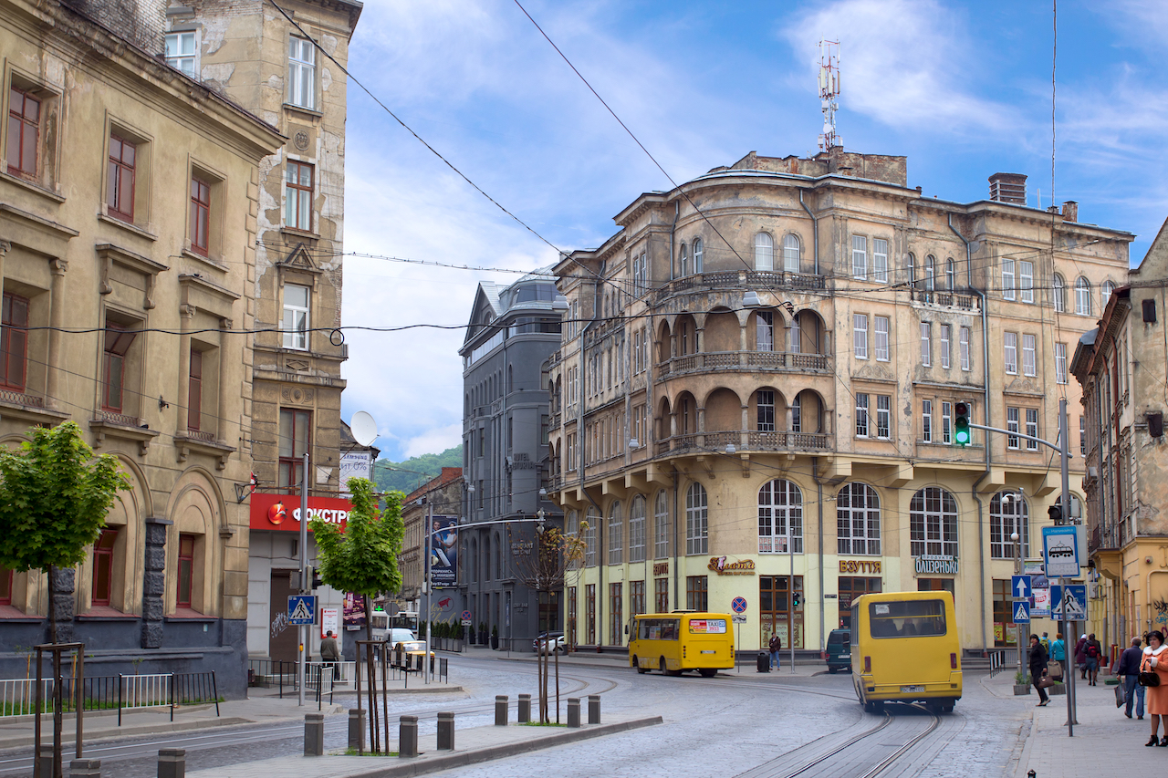 LVIV UKRAINE - MAY 8 2016: One of the streets of Lviv in the afternoon: shuttle buses on the road people waiting for transport and old-style buildings Ukraine