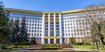 Parliament of the republic of moldova in chisinau, national flag, stefan cel mare street, spring time with blue sky