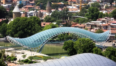 TBILISI GEORGIA Jul. 18 2017: Bridge of Peace is a bow-shaped pedestrian bridge a steel and glass construction over the Kura River in downtown Tbilisi capital of Georgia