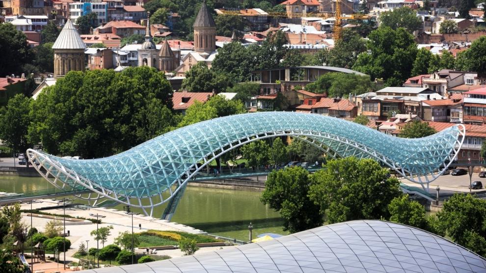 TBILISI GEORGIA Jul. 18 2017: Bridge of Peace is a bow-shaped pedestrian bridge a steel and glass construction over the Kura River in downtown Tbilisi capital of Georgia