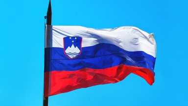 Slovenia flag against blue sky waving in wind