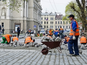 LVOV UKRAINE - APRIL 25: Workers masons laid paving stones in the repair of the main street on April 25 2013 in Lviv Ukraine