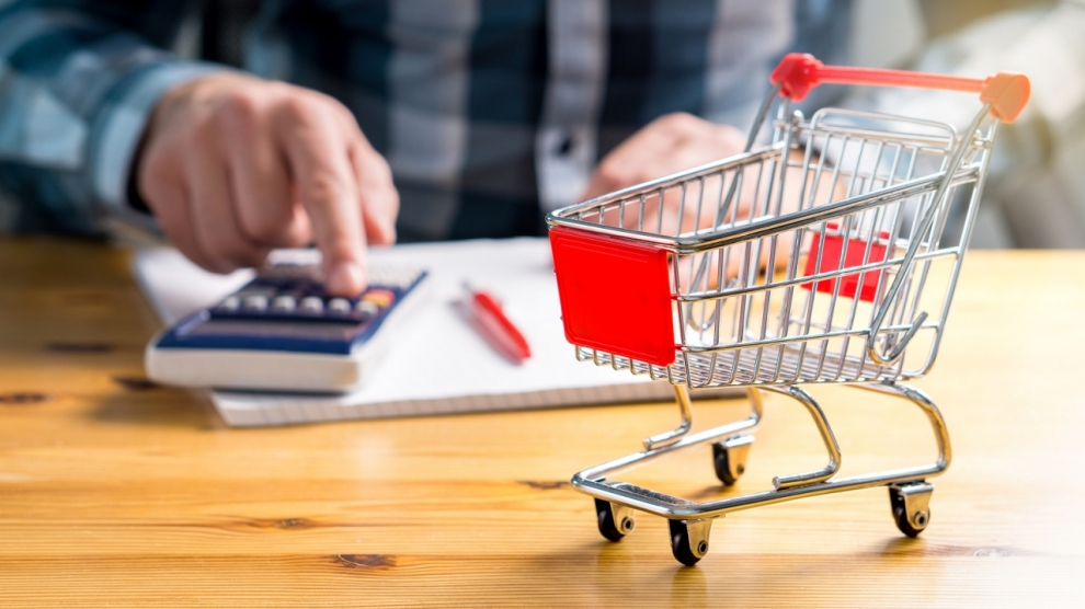 Rising food and grocery store prices is estonia and cost of living concept. Man counting food and consumer goods money with pen, paper and calculator at home. Budget of disadvantaged and low income family.