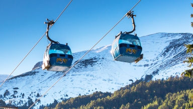 Bansko, Bulgaria - December, 6, 2015: Two Bansko cable car cabins and snow mountains peaks