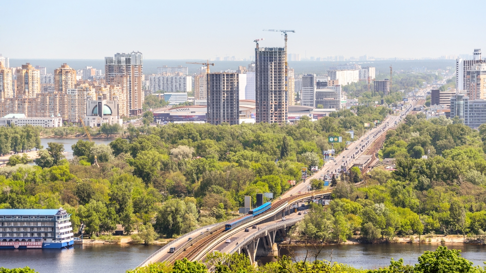 Kiev, Ukraine - May 15, 2017: Beautiful Kiev cityscape with bright green trees, river dnepr and buildings on the left river bank. Kiev, Ukraine.