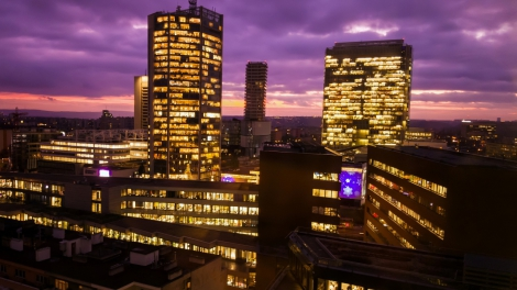 Prague skyscrapers in blue hour with purple sky. Modern building architecture after sunset. Office center in capital city. Czech republic lighting buildings.