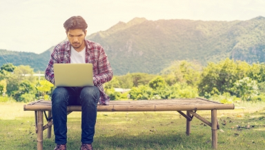 Young man working on his laptop connect to wireless internet in rural area. Internet connection allows people to work anywhere from laptop. Notebook and nature background. Wireless technology concept.