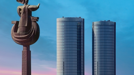 Riga Latvia - May 04 2017: Sculpture of Daugava and view to the Modern glass skyscrapers. Two round residential Z-Towers in the city center. Riga Latvia