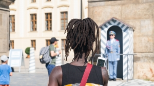 PRAGUE - AUGUST 29: Black woman in selective focus from behind with dreadlocks lifts mobile to yake photo of Guards Prague Castle Guard in blue uniform at attention while other tourists walk around looking at Prague Castle and the guards