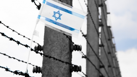 Small flag of Israel hanging on the barbwire in concentration camp